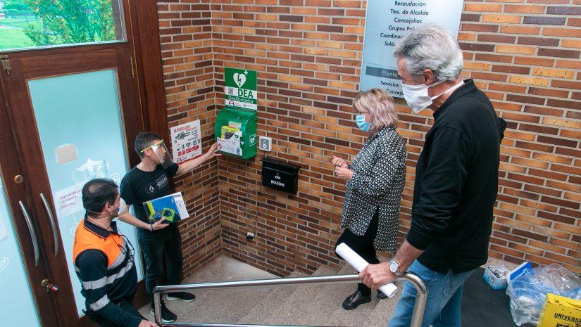 La alcaldesa y el concejal de Protección Civil atienden las explicaciones del técnico tras colocar el desfibrilador en el acceso al Ayuntamiento