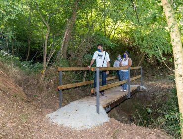 Los concejales de Medio Ambiente, Barrios y Empleo, Isabel Herrera Landeras, Fernando Sañudo Pérez y Pedro Roca Galnares, visitando el puente peatonal en el sendero al Pozo Tremeo