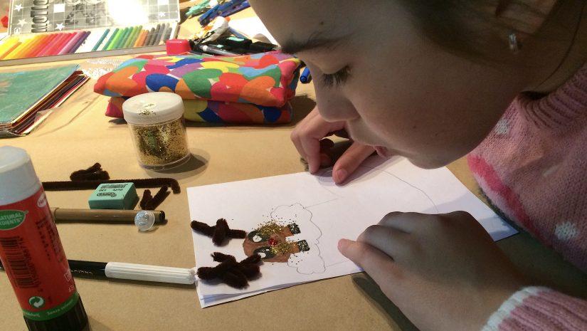 Un niño realiza una actividad cultural en la biblioteca municipal de Polanco
